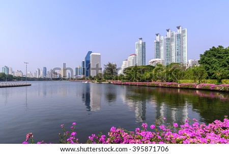 Bangkok skyline and water reflection with urban lake in summer.
