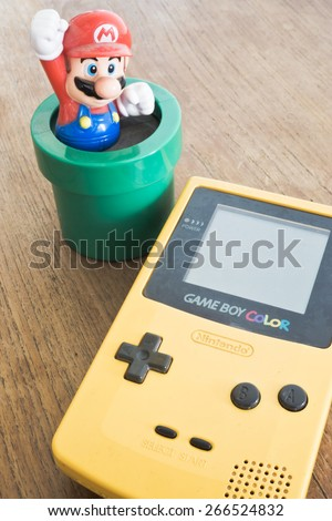 BANGKOK, THAILAND - APR 02: Photo of Game Boy Color device with Super Mario Bros figure. (Game Boy is a popular handheld game console manufactured by Nintendo) on April 02, 2015 in Bangkok, Thailand - stock photo