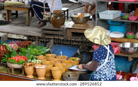 BANGKOK, THAILAND - APRIL 12: A local Thai cook preparing food in a boat at the Taling Chan Floating Market in Bangkok, Thailand on the 12th April, 2015.