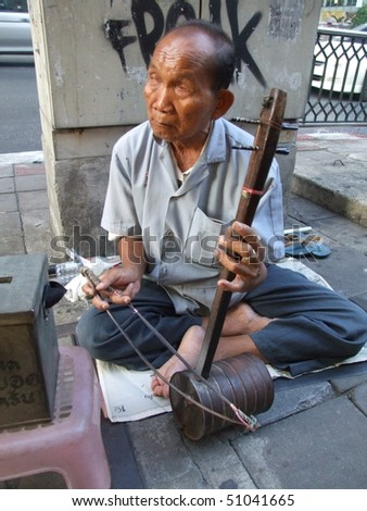 BANGKOK, THAILAND - APRIL 03: Elderly Thai blind man sits by the roadside and plays music for passing tourists and Thai people to make money. April 03 2007 in Bangkok. - stock photo