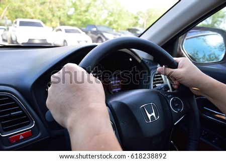 Bangkok, Thailand - April 10, 2017: Honda Black Steering Wheel And Silver Logo. Honda Motor Co., Ltd. is a Japanese public multinational conglomerate corporation. Man driving car.