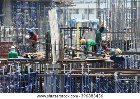 Bangkok, Thailand - April 5, 2013: Labourers work on a city centre construction site. The Thai capital is undergoing a construction boom with numerous new commercial and residential developments. - stock photo