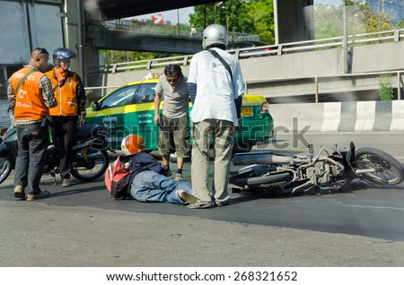 BANGKOK, THAILAND - APRIL 28: Motorcycle accidents on the street of Bangkok due to road slippery on April 28, 2012. People around that area gather to help the injury. - stock photo