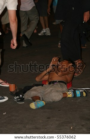 BANGKOK, THAILAND - APRIL 3: Thai crippled man lies and begs for money from tourists on Khaosarn road on April 3, 2009 in Bangkok. - stock photo