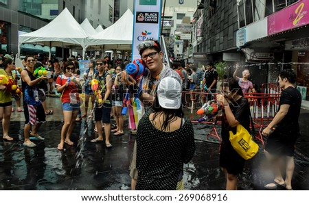 Bangkok, Thailand: April 15, 2014 - Tourists shooting water and having fun celebrating the traditional Thai New Year, Songkran, on Siam center in Bangkok, Thailand.