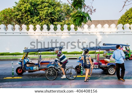 BANGKOK, THAILAND - APRIL 12, 2016 : Tricycle taxi of Thailand on street and background wall of Wat Phra Kaew ( the Temple of the Emerald Buddha). Here is destinations of landmarks traveler. - stock photo