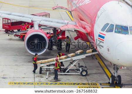 BANGKOK, THAILAND - April 11, 2014: unloading of baggage from the Airasia aircraft in Bangkok airport on April 11, 2014. Air Asia company is the largest low cost airlines in Asia. - stock photo