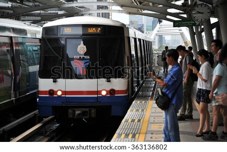 BANGKOK. THAILAND - AUG 7, 2013: A train approaches as rail travelers wait on a platform at a city centre BTS Skytrain station. Launched in 1999, the BTS has a daily ridership of 600,000 people. - stock photo