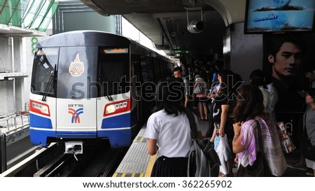BANGKOK, THAILAND - AUG 4, 2013: Rail travelers wait for an approaching train on a platform at a city centre BTS Skytrain station. Launched in 1999, the BTS has a daily ridership of 600,000 people. - stock photo