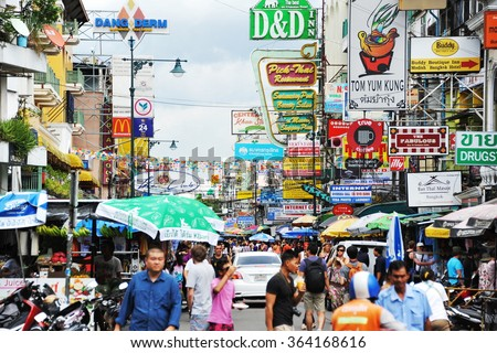 BANGKOK, THAILAND - AUG 21, 2013: Tourists and locals walk along popular backpacker destination Khao San Road. The area is famous for its street market, budget accommodation and lively bar scene. - stock photo