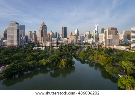 Bangkok Thailand city skyline at central business district of Sathorn street daylight in the morning. Drone aerial view. Public park Lumpini in the front.