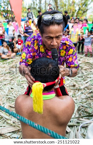 BANGKOK THAILAND- DEC 6: Unidentified trainer take off garland in Muaythai Tub Jark match (Muaythai stage covered with nypa plam leaves ) on December 6, 2014 at Suan Luang Rama 9 Bangkok Thailand - stock photo