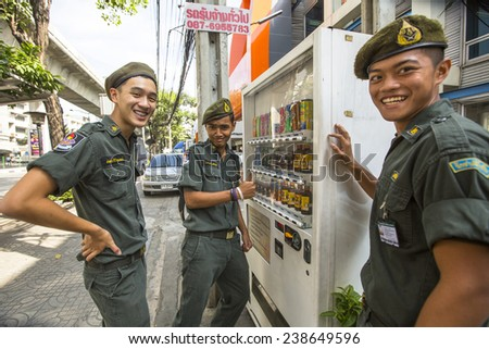 BANGKOK, THAILAND - DEC 17, 2014: Unidentified young Thai soldiers posing for camera on a street in the city center. Military service runs on a contract (65%) and mandatory. Draft age - 20-55 years.  - stock photo