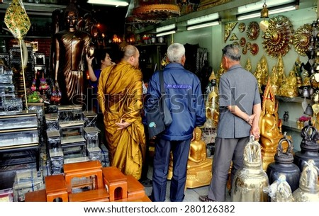 Bangkok, Thailand - December 18, 2009:  A monk with two Thai men shopping in a store specialising in religious artifacts on Thanon Bamrung Muang Street - stock photo