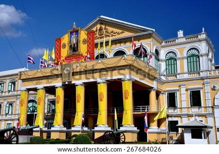Bangkok, Thailand - December 20, 2008:  A portrait of Thailand's beloved King Bhumibol Adulyadej stands atop the portico entrance to the 19th century neo-colonial Defense Ministry - stock photo