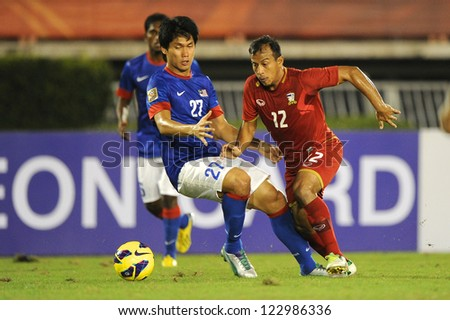 BANGKOK THAILAND-DECEMBER 13:Adul Lahso of Thailand (red) in action during the AFF Suzuki Cup between  Malaysia and Thailand at  at Supachalasai stadium on Dec13, 2012  in Bangkok,Thailand.