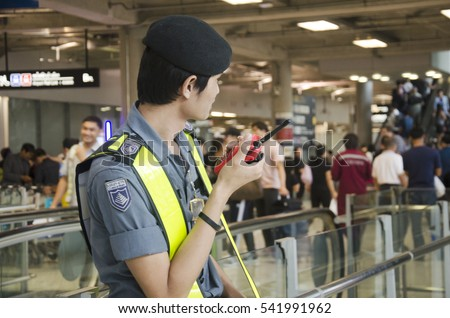 BANGKOK, THAILAND - DECEMBER 11 : Airport security guard standing and use walkie-talkie for security and protect people at international airport on December 11, 2016 in Bangkok, Thailand
