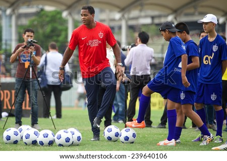 BANGKOK,THAILAND - DECEMBER 04: Patrick Kluivert (red)poses with local child at the Global Legends Series coaching clinic, at the Thailand Sports Authority, on December 4, 2014 in Bangkok, Thailand. - stock photo