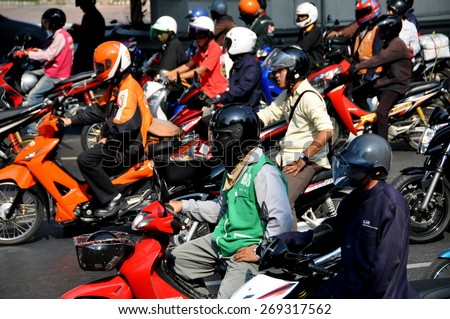 Bangkok, Thailand - December 23, 2009:  People wearing mandatory helmets seated on their motorbikes waiting patiently at a traffic light on Silom Road - stock photo