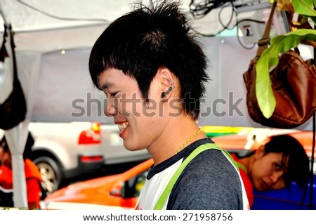 Bangkok, Thailand - December 17, 2011: Smiling Thai youth with multiple earrings and a nose piercing selling food on Rama IV Road at San Yan