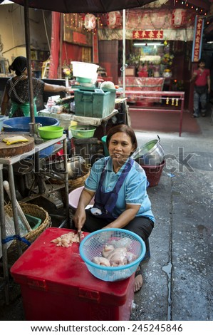 BANGKOK, THAILAND - DECEMBER 25, 2014: Street Photography of Street market in China town.  A woman prepares a dish of chicken. - stock photo