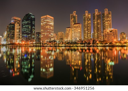 BANGKOK, THAILAND - DECEMBER 3 : The business skyscraper skyline are in Bangkok city downtown with reflection on wide lake in night time in Bangkok, Thailand on December 3,2015