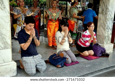 Bangkok, Thailand - December 16, 2011:  Three Thai Buddhists, their hands clasped in prayer, kneel on fabric mats in front of the Khong dancing pavilion at the holy Erawan Shrine - stock photo