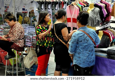 Bangkok, Thailand - December 23, 2013:  Three Thai women shopping for bargain clothing at an outdoor street market on Thanon Ratchaprasong - stock photo