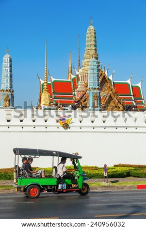 BANGKOK, THAILAND - DECEMBER 10, 2014: traditional tuk-tuk on the road in front of the famous Buddhist Temple Wat Phra Kaew, one of the main landmarks of Bangkok, Thailand - stock photo