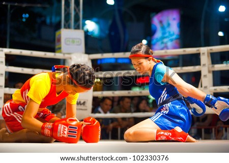 BANGKOK, THAILAND - DECEMBER 8, 2010: Two unidentified female muay thai fighters side by side perform a kickboxing ritual called the wai khru on December 8, 2010 in Bangkok, Thailand - stock photo