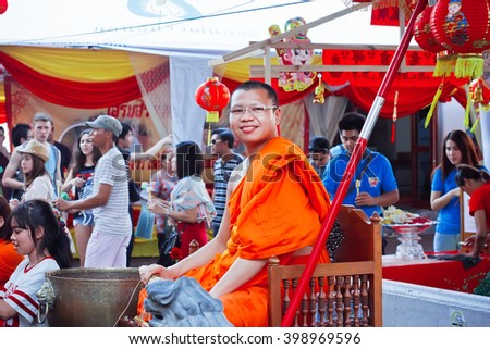 BANGKOK, THAILAND - FEB 14: Buddhist monk smiling at the crowd of people of historical monastery Wat Pho on February 14, 2015. Wat Pho is a Buddhist temple complex founded in 16th century - stock photo