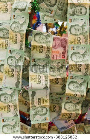 BANGKOK, THAILAND - 8 FEB 2016: Chains of Thai Paper Money Hung offering in buddhist temple for Good Luck - stock photo