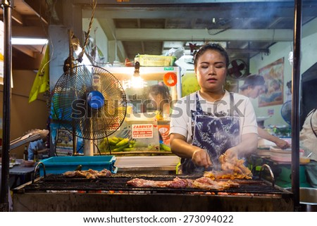 BANGKOK,THAILAND,FEBRUARY 16,2015: A woman is cooking chicken brochettes on barbecue in a small restaurant of the Sukhumvit Soi 38 in Bangkok,Thailand - stock photo