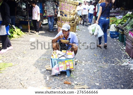 BANGKOK, THAILAND- FEBRUARY 17, 2015: Khlong Toei food market. Local Thai man sitting in the middle of the walking path in the market and eating his lunch. Other people around him continue shopping.  - stock photo