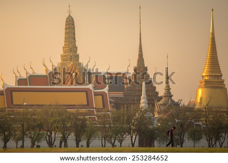 Bangkok, Thailand - February 7, 2015 : Man is alone and background is Wat Phra Kaew ( the Temple of the Emerald Buddha) in morning. Here is destinations of landmarks traveler.