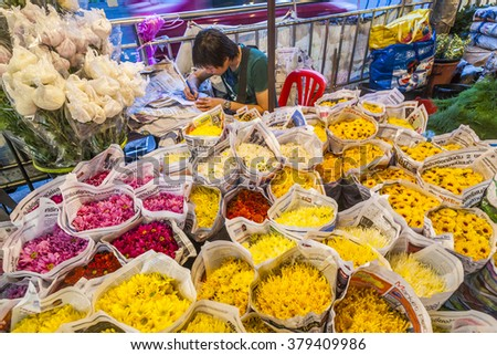 BANGKOK, THAILAND - JAN 4, 2010: man sells colorful flowers at the flowermarket Pak Khlong Talat in Bangkok early morning. It is the biggest flower market in Thailand.