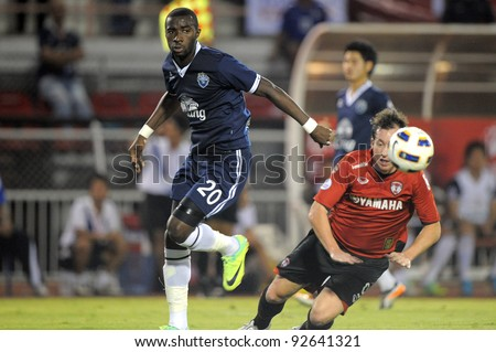 BANGKOK, THAILAND - JAN 11:  Obama Joseph Florent of the Buriram PEA (L) in action during the Thaicom FA Cup Final match  between MuangThong United at National Stadium on Jan11,2012 in Bangkok Thailand. - stock photo