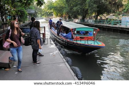 Bangkok, Thailand - January 25, 2011: A canal boat on Klong Saen Saep arrives for passengers waiting on a pier. Klong Saen Saep canal runs for 18 kilometers through central Bangkok. - stock photo