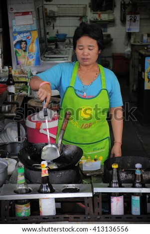 Bangkok, Thailand - January 20, 2011: A cook prepares food at a city centre restaurant. The Thai capital is a main driver of Thailand's economy with a GDP worth 29% of the country's total output. - stock photo