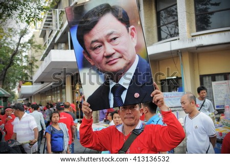 Bangkok, Thailand - January 23, 2011: A protester holds up a portrait of self exiled former Prime Minister Thaksin Shinawatra during a large anti government Red Shirt rally at Democracy Monument.  - stock photo