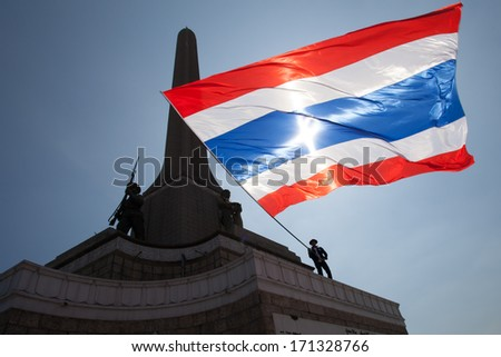 Bangkok, Thailand � January 13, 2014: Anti-government protester waves a big Thai flag on the Victory monument in Bangkok - stock photo