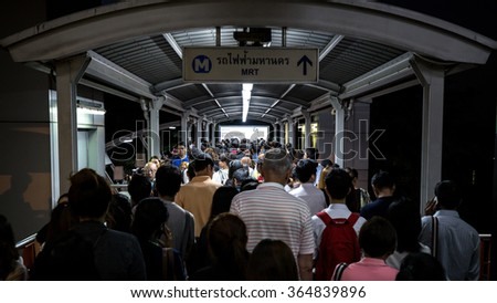 Bangkok, Thailand - January 18, 2016 : Crowd of people walking out from BTS Mo Chit station to the road by footbridge in rush hour at night with advertising board and information sign above the head - stock photo