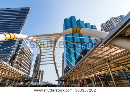 Bangkok, Thailand - January 22, 2016: High rise buildings and a sky walk in midtown of Bangkok. Sky walk is the connecting walkway, intersection road of train and rapid bus.