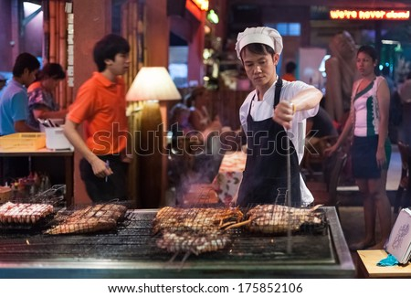 BANGKOK, THAILAND - JANUARY 9, 2012: Man prepares traditional Thai food on Khao San Road food stall. Everyday thousands of tourists and locals buys food on these stalls. - stock photo