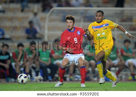 BANGKOK THAILAND-JANUARY 15:Sompong Solep (yellow) of Thailand  in action during the 41st King's cup match between Thailand and Korea Rep at Rajamangala stadium on Jan15,2012 in Bangkok,Thailand.