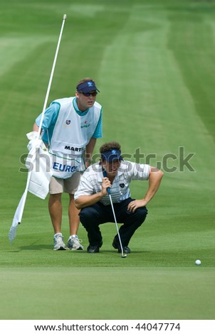 BANGKOK, THAILAND - JANUARY 8: Spanish golf player Pablo Martin and his caddie preparing a put at the Royal Trophy tournament, Asia vs Europe, at Amata Spring on January 8, 2010 in Bangkok, Thailand.