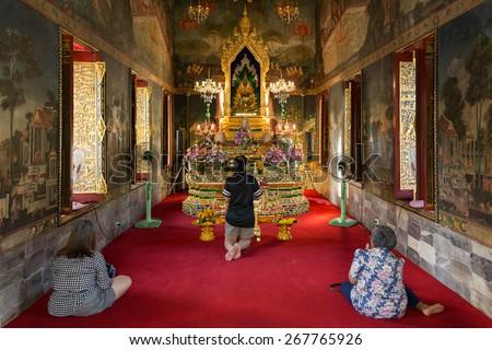 BANGKOK, THAILAND, JANUARY 14, 2015: Three Thai women are praying in the Wat pathum wanaram Bouddhist temple in Bangkok, Thailand. - stock photo