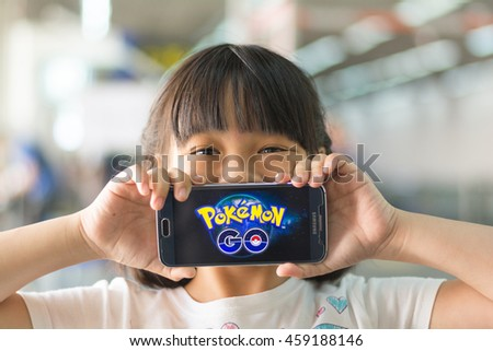 BANGKOK, THAILAND - July 22, 2016:  A girl hold smart phone gadget on hands with screen showing application Pokemon Go mobile game app developed by Niantic for iOS and Android devices - stock photo