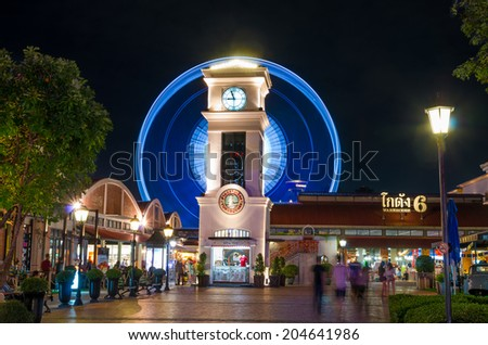 BANGKOK, THAILAND - JULY 10 : The clock tower with ferris wheel and warehouse background at the asiatique river front on July 10, 2014 Bangkok, Thailand