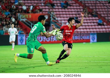 BANGKOK,THAILAND-JULY 23:Unidentified player of MTUTD in action with BEC TERO player between the game SCG Mungthong United and BEC TERO at SCG Mungthong Stadium on Jul 23, 2013 in,Thailand.